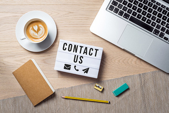 Contact Us sign surrounded by laptop, coffee, notepad, and office supplies